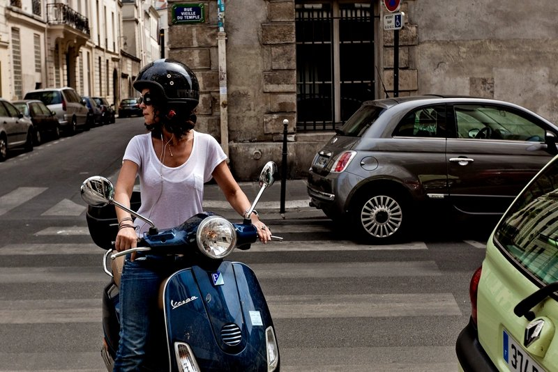 A traveler on a retro scooter in Paris.
